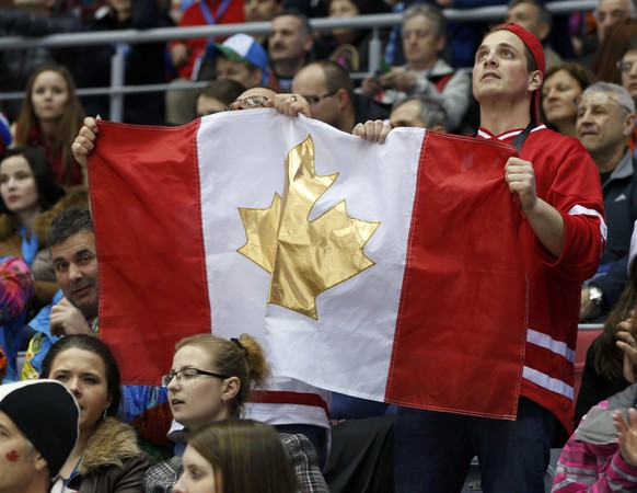 Fans raise a Canadian flag featuring a gold maple leaf as they watch the men's preliminary round ice hockey game between Canada and Norway at the Sochi 2014 Sochi Winter Olympics, February 13, 2014.     REUTERS/Gary Hershorn (RUSSIA  - Tags: OLYMPICS SPORT ICE HOCKEY)