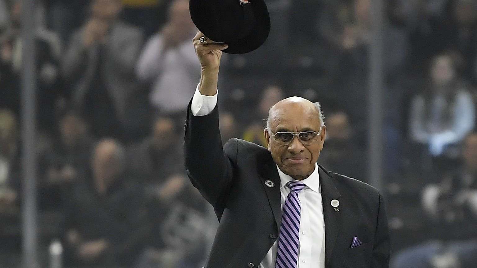 FILE - In this Feb. 22, 2018, file photo, former hockey player Willie O'Ree waves to the crowd after being honored prior to an NHL hockey game between the Los Angeles Kings and the Dallas Stars, in Los Angeles. O'Ree was selected to the Hockey Hall of Fame, Tuesday, June 26, 2018. (AP Photo/Mark J. Terrill, File)