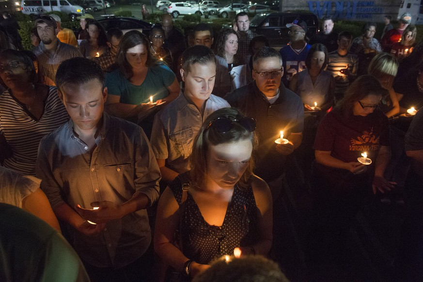 People attend a candlelight vigil in front of the WDBJ-TV station in Roanoke, Va., Thursday, Aug. 27, 2015, a day after reporter Alison Parker and cameraman Adam Ward from the station were killed during a live broadcast. Vester Flanagan filmed himself gunning down the journalists and posted the video on social media after fleeing the scene. (AP Photo/Don Petersen)