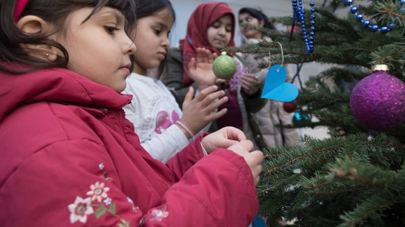 epa05677112 Refugee children decorate a Christmas tree at a preliminary reception centre in Berlin, Germany, 15 December 2016. The decorating was part of the presentation of the first 'Game and coaching mobile' for refugee children and teenagers, which visits refugee homes in various districts of Berlin with its creative offers. The vehicle is a joined project of the children relief organisation World Vision and the organisation blu:box.  EPA/JOERG CARSTENSEN