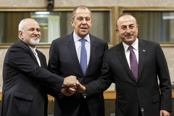 epa07238662 Iranian Foreign Minister Mohammad Javad Zarif, (L), Russian Foreign Minister Sergei Lavrov, (C), and Turkish Foreign Minister Mevlut Cavusoglu, (R), shakes hands after a joint statement following the consultations on Syria, at the European headquarters of the United Nations in Geneva, Switzerland, 18 December 2018. High-level representatives of Russia, Turkey and Iran meet with the UN Special Envoy for Syria on the situation in Syria.  EPA/SALVATORE DI NOLFI