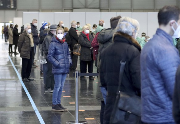 """People are waiting for a mass Covid-19 testing from soldiers of the Austrian army in Vienna, Austria, Friday, Dec 4, 2020. Written on the poster """" corona test street"""". Austria conducts a mass Covid-19 testing exercise to better understand the spread of the virus in the country. (AP Photo/Ronald Zak)"""