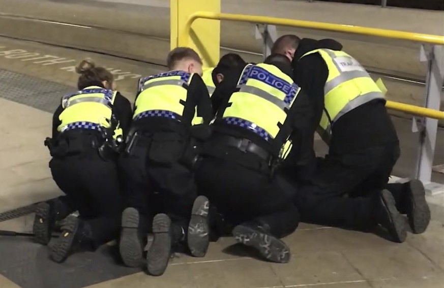 UGC issued by PA shows Police restraining a man after he stabbed three people at Victoria Station in Manchester, England, late Monday Dec. 31, 2018. Two commuters - a man and woman in their 50s - were taken to hospital with knife injuries and a British Transport Police (BTP) officer was stabbed in the shoulder. Police said a man was arrested on suspicion of attempted murder and remains in custody. (Sam Clack/PA via AP)