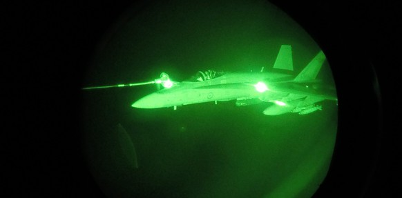 epa04926555 A handout image released by the Royal Australian Air Force (RAAF) on 12 September 2015 shows a night vision image of a F/A-18A Hornet from Australia's Air Task Group refuelling from a Royal Australian Air Force KC-30A Multi Role Tanker Transport aircraft during the first missions of Operation OKRA over Syria, 11 September 2015. The Australian Defense Force Operation OKRA started in August 2014 with the aim to combat IS in Iraq and the Levant.  EPA/RAAF / SGT Pete AUSTRALIA AND NEW ZEALAND OUT HANDOUT EDITORIAL USE ONLY/NO SALES