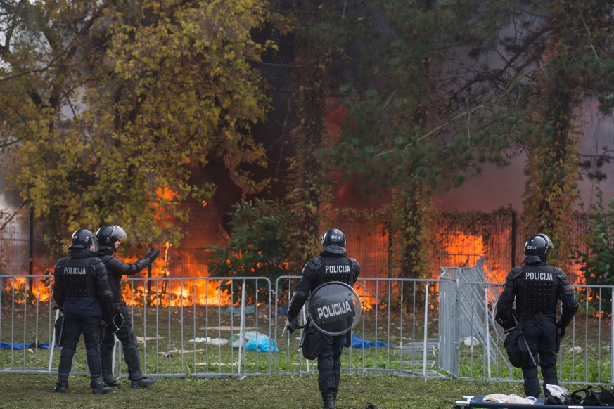 Slovenain police watch the fire at a camp for migrants near Slovenia's border with Croatia, in Brezice, Slovenia, Wednesday, Oct. 21, 2015. It was not clear what caused the fire  in the camp , which is housing thousands of migrants, including women and children.  (AP Photo/Matej Leskovsek)