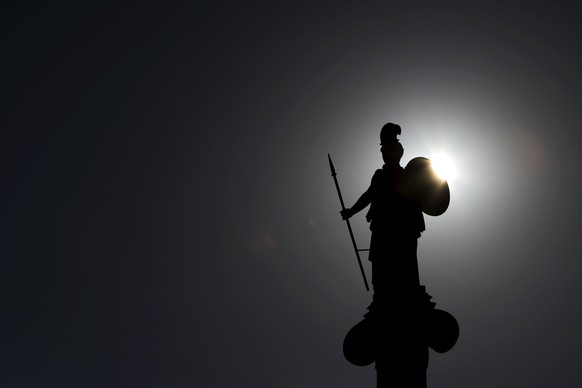 A statue of Godess Athena is silhouetted against the rising sun in Athens, Greece June 25, 2015. Greece's ruling Syriza party dismissed reform demands from the country's international creditors as