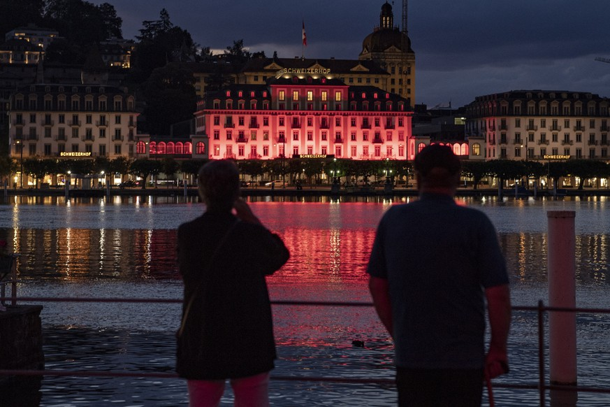 epa08502911 The Hotel Schweizerhof is pictured lit up in red during the action 'Night of light' campaign, in Luzern, Switzerland, 22 June 2020, 22 June 2020. Monday evening numerous public monuments and companies from the event industry are illuminated in red in support of culture during the event 'Night of Light' that takes place throughout Switzerland.  EPA/URS FLUEELER