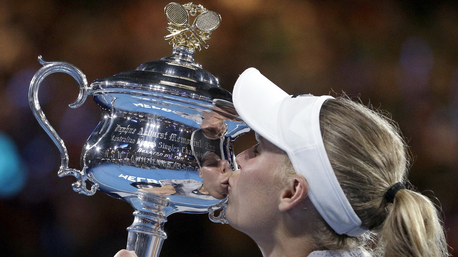 Denmark's Caroline Wozniacki kisses her trophy after defeating Romania's Simona Halep in the women's singles final at the Australian Open tennis championships in Melbourne, Australia, Saturday, Jan. 27, 2018. (AP Photo/Dita Alangkara)
