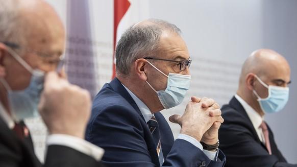 Bundesrat Ueli Maurer, Bundespraesident Guy Parmelin und Bundesrat Alain Berset, von links, sprechen an einer Medienkonferenz zu Covid 19 Massnahmen, am Mittwoch, 27. Januar 2021, in Bern. (KEYSTONE/Peter Schneider)
