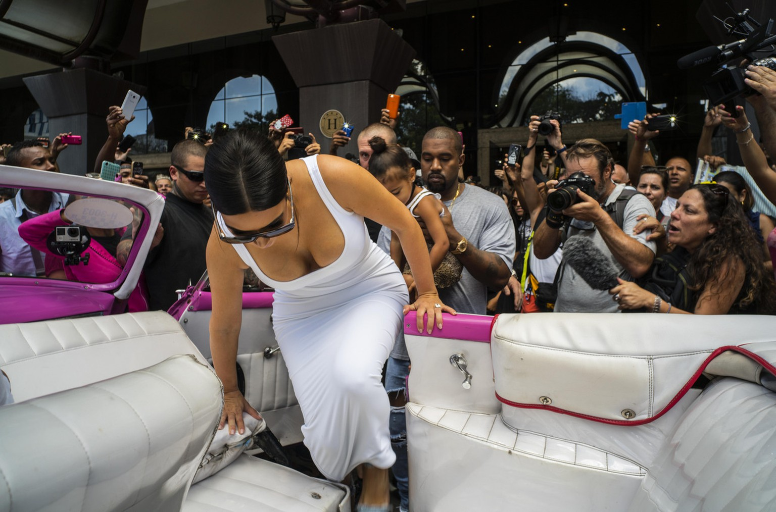 American reality-show star Kim Kardashian gets into a classic car, followed by her husband, rap singer Kanye West and their daughter North West in Havana, Cuba, Thursday, May 5, 2016. West, Kardashian and members of her reality-show-star family have become the latest celebrities to visit Havana. (AP Photo/Ramon Espinosa)