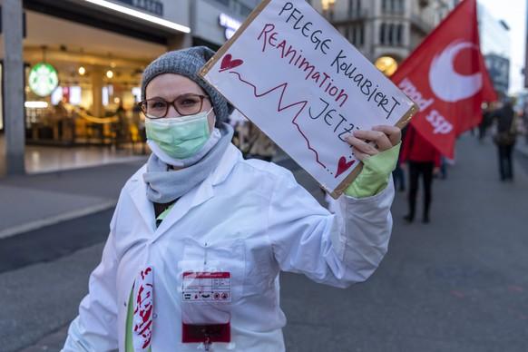 Eine Teilnehmerin haelt ein Plakat mit der Aufschrift Pflege kollabiert. Reanimation jetzt! bei einem Gesundheitsmarsch fuer die Solidaritaet mit dem Gesundheitspersonal in Basel, am Dienstag, 27. Oktober 2020. Die Gewerkschaften VPOD, Syna und der Berufsverband SBK rufen diese Woche in der ganzen Schweiz zu Aktionen im Gesundheitsbereich auf. (KEYSTONE/Georgios Kefalas)