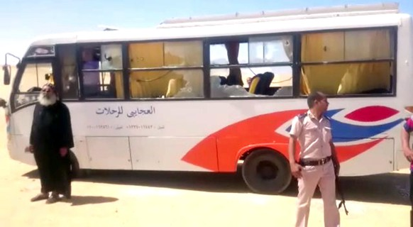 epa05991662 Security officials stand at the site of an armed attack on a bus near the Monastery of St Samuel the Confessor, in Minya Province, central Egypt, 26 May 2017. According to news reports, a group of Coptic Christians were attacked in their bus en route to the Monastery when gunmen opened fire on them, killing at least 20 and injuring dozens.  EPA/STR EGYPT OUT BEST QUALITY AVAILABLE