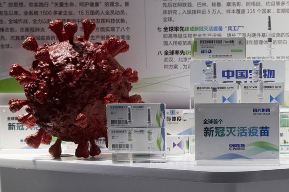 Samples of a COVID-19 vaccine produced by Sinopharm subsidiary CNBG are displayed near a 3D model of a coronavirus during a trade fair in Beijing on Sept. 6, 2020. State-backed Sinopharm's subsidiary CNBG has injected 350,000 people outside its clinical trials for COVID-19 vaccine, which have about 40,000 people enrolled. It's a highly unusual move that raises ethical and safety questions, as companies and governments worldwide race to develop a vaccine that will stop the spread of the new coronavirus. (AP Photo/Ng Han Guan)