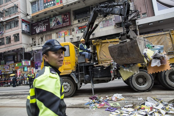 epa04530015 A worker loads dismantled barricades and tents left behind by protesters at the Occupy Central site in Causeway Bay, Hong Kong, China 15 December 2014. Around 400 officers swiftly cleared the100 metre-long occupied site. Students and civic groups are launching a