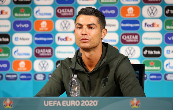 epa09275477 A handout photo made available by the UEFA shows Portugal's Cristiano Ronaldo with a bottle of water during the Portugal Press Conference ahead of the UEFA Euro 2020 Group F match between Hungary and Portugal, at Puskas Arena in Budapest, Hungary, 14 June 2021 (issued 16 June 2021).  EPA/UEFA HANDOUT Strictly for Editorial Use Only. No use in publications devoted solely to any single team, player and/or match. Use in online, mobile and/or apps must be comparable to that in a newspaper or permitted magazines and books Getty Images provides access to thi HANDOUT EDITORIAL USE ONLY/NO SALES