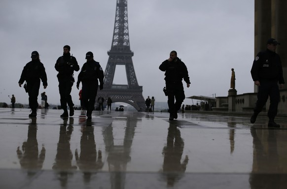French police officers patrol on the esplanade of the Trocadero in Paris, France Sunday, May 7, 2017. Security was high as voters across France vote for a new president in an unusually tense and important election that could decide Europe's future, making a stark choice between pro-business progressive Emmanuel Macron and far-right populist Marine Le Pen. (AP Photo/Emilio Morenatti)