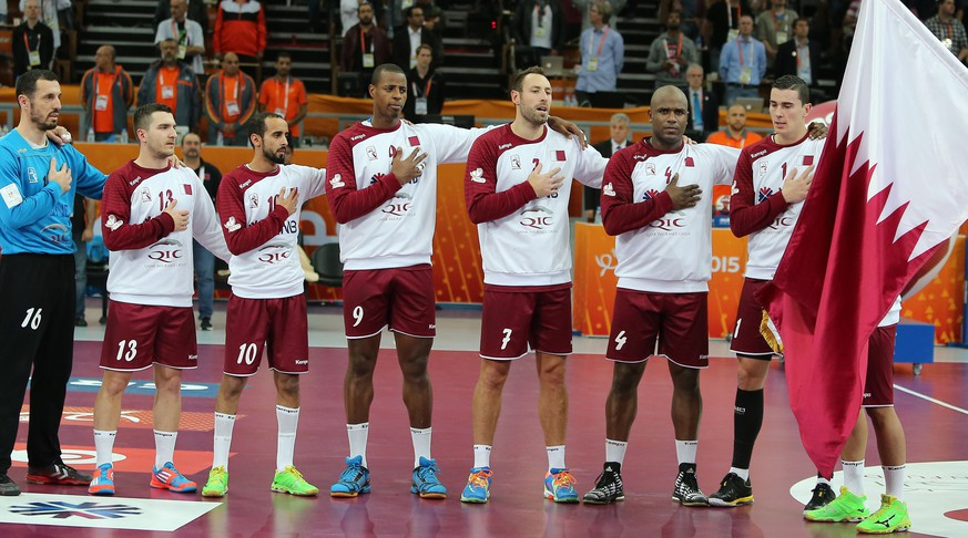Players for the Qatar team stand at attention for the national anthem before the 24th Men's Handball World Championships quarterfinals match between Germany and Qatar at the Lusail Multipurpose Hall in Doha on January 28, 2015.  AFP PHOTO / AL-WATAN DOHA / KARIM JAAFAR