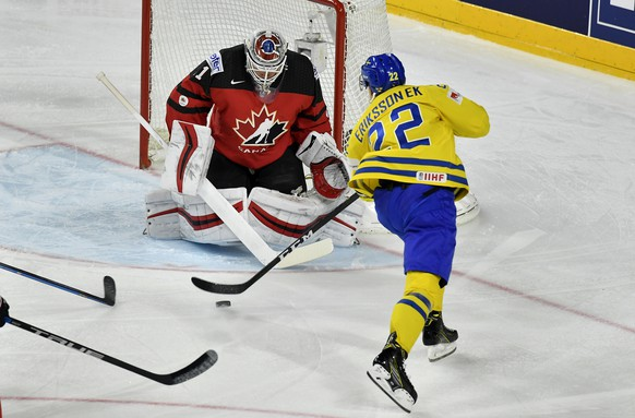 Canada's Calvin Pickard blocks a shot by Sweden's Joel Eriksson Ek, right, at the Ice Hockey World Championships final match between Canada and Sweden in the LANXESS arena in Cologne, Germany, Sunday, May 21, 2017. (AP Photo/Martin Meissner)