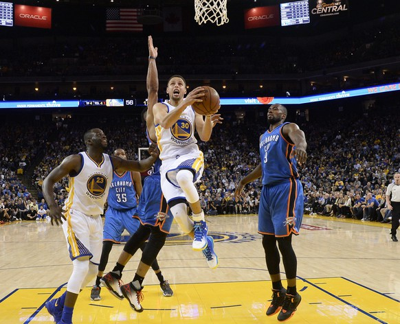 epa05193527 Golden State Warriors guard Stephen Curry (C) goes to the basket for two points against the Oklahoma City Thunder during their NBA game at Oracle Arena in Oakland, California, USA, 03 March 2016.  EPA/JOHN G. MABANGLO CORBIS OUT