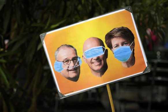 Demonstrators with a poster of three federal councillors at a protest against the Coronavirus lockdown in Bern, Switzerland, 23 May 2020. In Switzerland from 11 May, loosening measures slowing down the ongoing pandemic of the COVID-19 disease, which is caused by the SARS-CoV-2 coronavirus, become effective by step. (KEYSTONE/Anthony Anex)