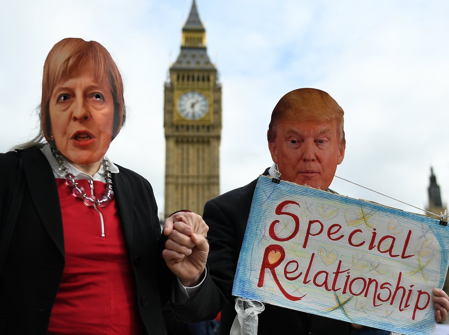 epa05805537 Protesters wearing masks depicting British Prime Minister Theresa May (L) and US President Donald J. Trump (R) and holding hands demonstrate against the proposed State visit to the UK of Donald Trump in London, Britain, 20 February 2017.  Parliament is debating the proposed state visit of US President Donald J. Trump to Britain. Nearly two million Britons have signed a petition against his visit.  EPA/ANDY RAIN