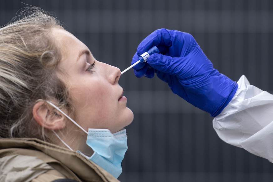 A woman gets a nasal swab at the corona test center at Central Station in Cologne, Germany, Friday, Oct. 23, 2020. According to the Robert Koch Institute, Germany's federal government agency and research institute responsible for disease control and prevention, the number of new infections with the corona virus in Cologne has risen to 120.1 per 100,000 inhabitants. (Marius Becker/dpa via AP)
