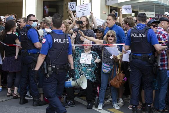 Polizisten halten Absperrbänder, um Demonstranten vom Bundesplatz fernzuhalten.