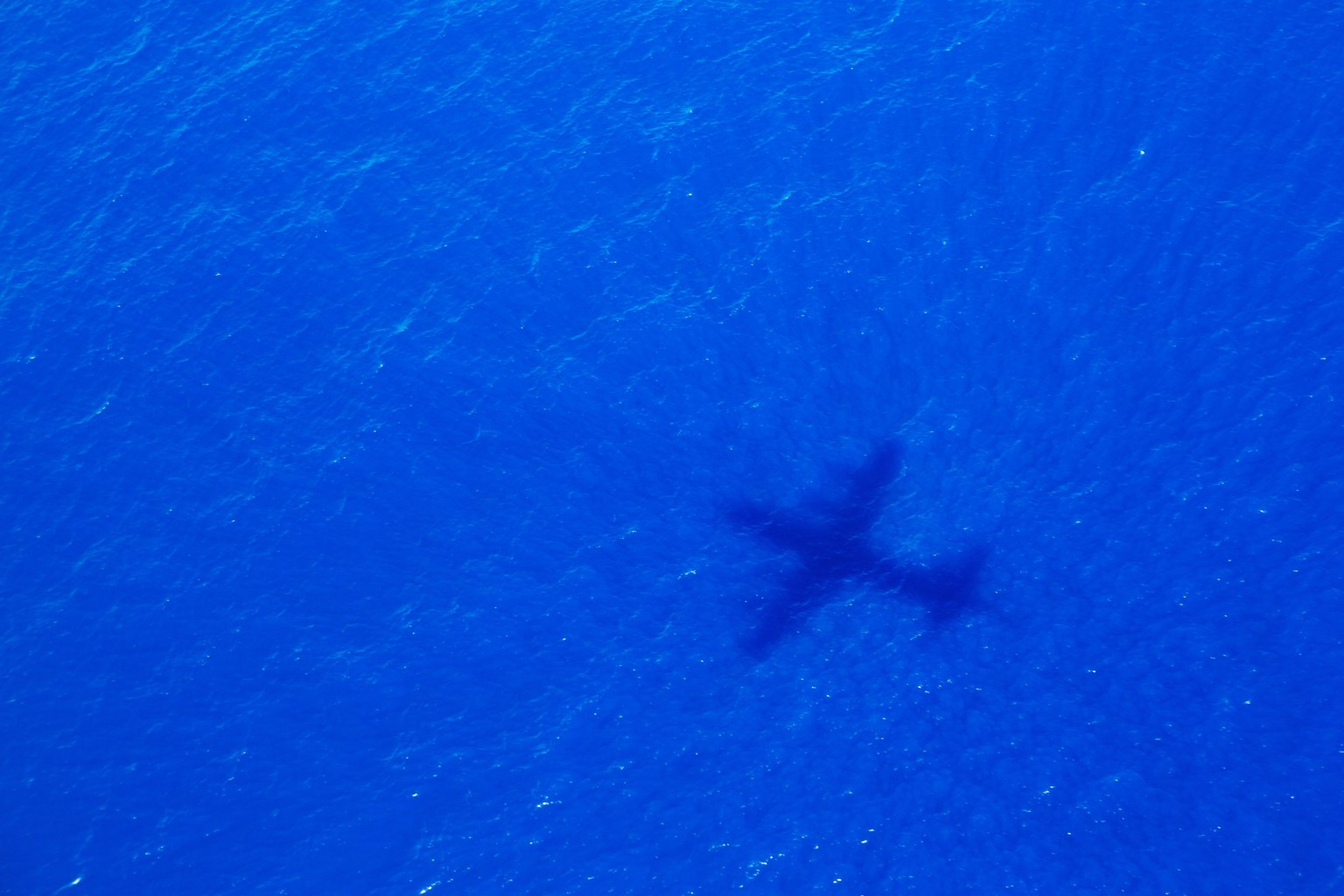 epa04164276 A picture made available 12 April 2014 shows the shadow of a Royal New Zealand Air Force P-3 Orion taking part in the search trying to locate missing Malaysia Airways Flight MH370, cast over the Indian Ocean, 11 April 2014. Their search area was located 1,800km North West of Perth and they were tasked with flying at 800ft to visually search for aircraft debris. The search for a missing Malaysia Airlines jet in the Indian Ocean kept its intensity on 12 April despite no new acoustic signals for three days. Ten planes and 14 ships were out looking for traces of MH370, which went missing more than a month ago after takeoff from Kuala Lumpur en route Beijing with 239 people on board.  EPA/RICHARD WAINWRIGHT / POOL AUSTRALIA AND NEW ZEALAND OUT