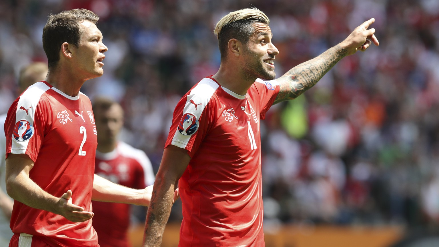 Switzerland's Stephan Lichtsteiner, left, and Valon Behrami gesture during the Euro 2016 round of 16 soccer match between Switzerland and Poland, at the Geoffroy Guichard stadium in Saint-Etienne, France, Saturday, June 25, 2016. (AP Photo/Thanassis Stavrakis)