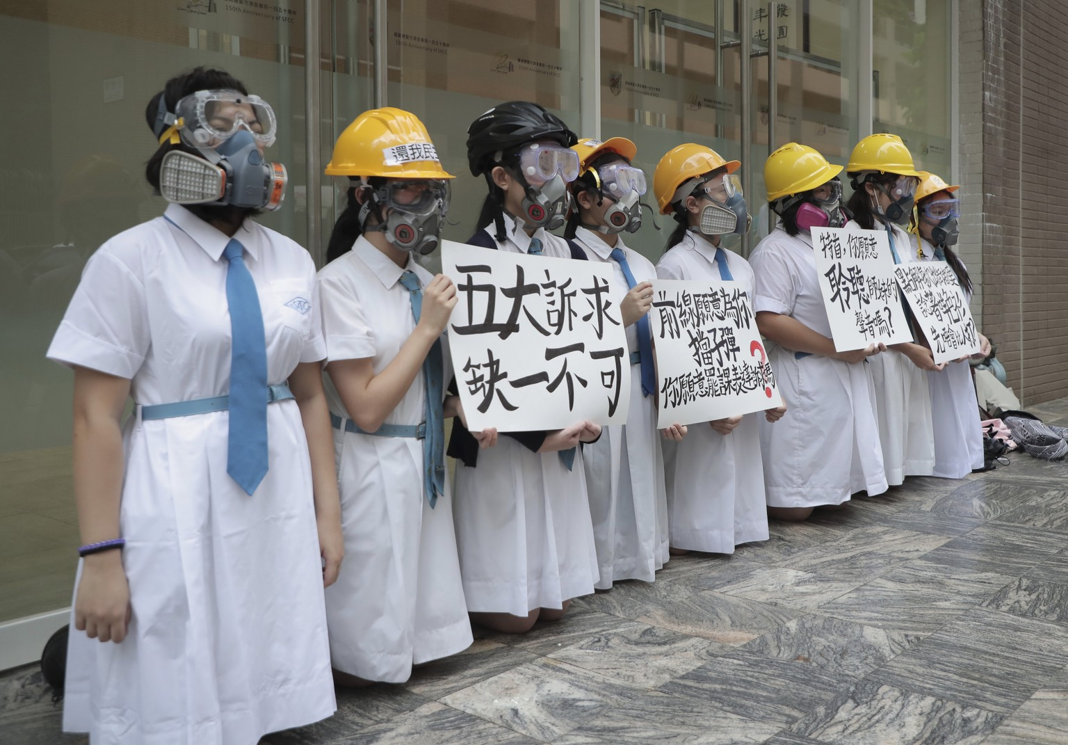 Students wearing gas masks and helmets hold a banner which reads