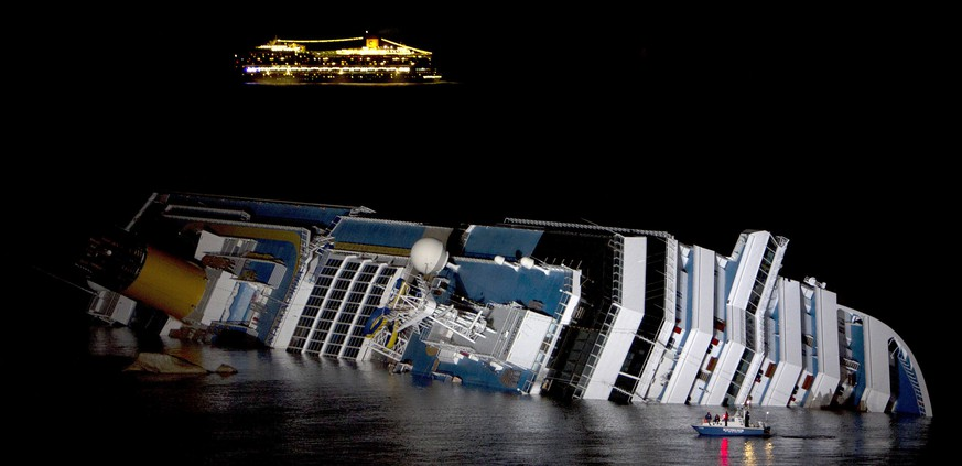 The cruise ship Costa Serena sails as its sister ship Costa Concordia cruise ship lays on its side after it ran aground off the west coast of Italy at Giglio island in this January 18, 2012 file photo.  An Italian prosecutor has asked a court to sentence the captain of the Costa Concordia  to more than 26 years in jail for his role in the 2012 disaster that killed 32 people. The defence is expected to respond in court starting February 9, with a verdict expected thereafter.  REUTERS/Stringer/Files (ITALY - Tags: DISASTER MARITIME)