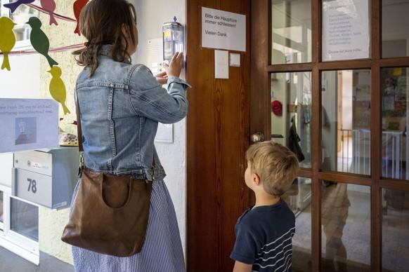 ZUM BETRIEB IN GFZ KINDERTAGESSTAETTEN WAEHREND DER CORONA-PANDEMIE STELLEN WIR IHNEN FOLGENDES NEUES BILDMATERIAL ZUR VERFUEGUNG - WEITERE BILDER FINDEN SIE AUF visual.keystone-sda.ch --- Eine Mutter und ihr Sohn desinfizieren beim Eingang der GFZ Kindertagesstaette 8 die Haende vor dem Betreten, fotografiert waehrend der Coronavirus-Pandemie am 17. April 2020 in Zuerich. (KEYSTONE/Christian Beutler)