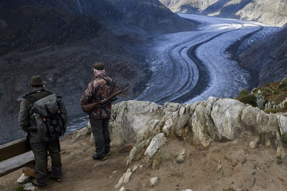 Two Hunters observe the wildlife next to the Swiss Aletsch Glacier during an autumn day above Bettmeralp in Wallis, Switzerland, on Monday, 23 September 2019. The Swiss Aletsch glacier, one of the largest ice streams in Europe, is the first Unesco World Heritage Site of the Alps. This huge river of ice that stretches over 23 km from its formation in the Jungfrau region (at 4000 m) down to the Massa Gorge in Wallis, around 2500 m below, fascinates and inspires every visitor. (KEYSTONE/Anthony Anex)