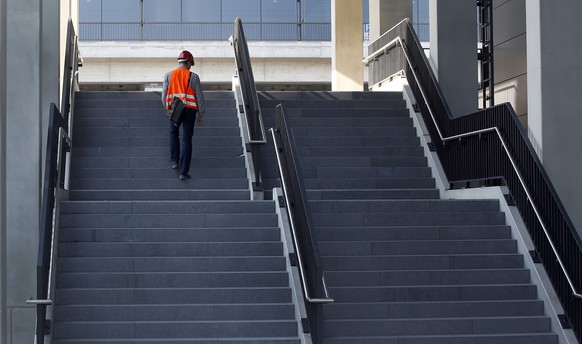 ZUM 10. JAHRESTAG DES BAUBEGINNS DES FLUGHAFENS BERLIN BRANDENBURG AM 5.SEPTEMBER 2016 STELLEN WIR IHNEN FOLGENDES BILDMATERIAL ZUR VERFUEGUNG: - A worker walks on the stairs to the ground level entrance of the Airport Berlin Brandenburg 'Willy Brandt', IATA code BER, in Schoenefeld, Germany, Wednesday, Oct. 2, 2013. (AP Photo/Michael Sohn)
