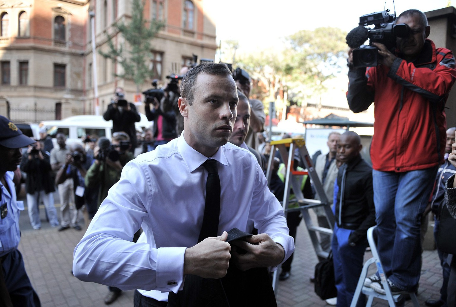 epa04163043 South African Paralympic athlete Oscar Pistorius (C) arrives at court for another day of cross examination in his ongoing murder trial, Pretoria, South Africa, 11 April 2014. Pistorius stands trial for the premeditated murder of his model girlfriend Reeva Steenkamp in February 2013.  EPA/STR SOUTH AFRICA OUT