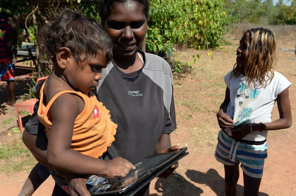 epa04297630 18-month old Nevaeh Dickson plays with an iPad held by her mother Tara Black, in the aboriginal community of Peppimenarti, about 320km south-west of Darwin, Australia, 04 July 2014. Peppimenarti is one of eight Aboriginal communities including Papunya and Palumpa to receive access to 3G mobile phone services through a Nothern Territory (NT) government joint project with Telstra worth 5.76 million Dollars.  EPA/DAN PELED AUSTRALIA AND NEW ZEALAND OUT