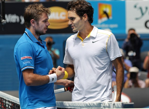 Roger Federer of Switzerland, right, and  compatriot Stanislas Wawrinka shake hands at the net after Federer won their quarterfinal match at the Australian Open tennis championships in Melbourne, Australia, Tuesday, Jan. 25, 2011.   (AP Photo/Shuji Kajiyama)