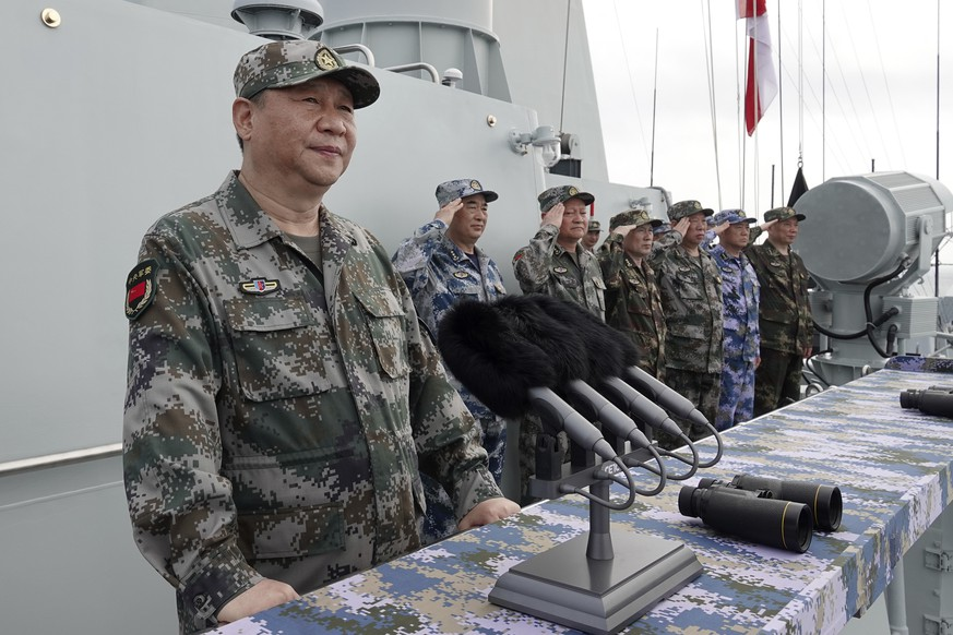 In this April 12, 2018 photo released by Xinhua News Agency, Chinese President Xi Jinping, left, speaks after he reviewed the Chinese People's Liberation Army (PLA) Navy fleet in the South China Sea. China has announced live-fire military exercises in the Taiwan Strait amid heightened tensions over increased American support for Taiwan. The announcement by authorities in the coastal province of Fujian on Thursday was accompanied by a statement that the navy was ending a three-day exercise in the South China one day early. (Li Gang/Xinhua via AP)