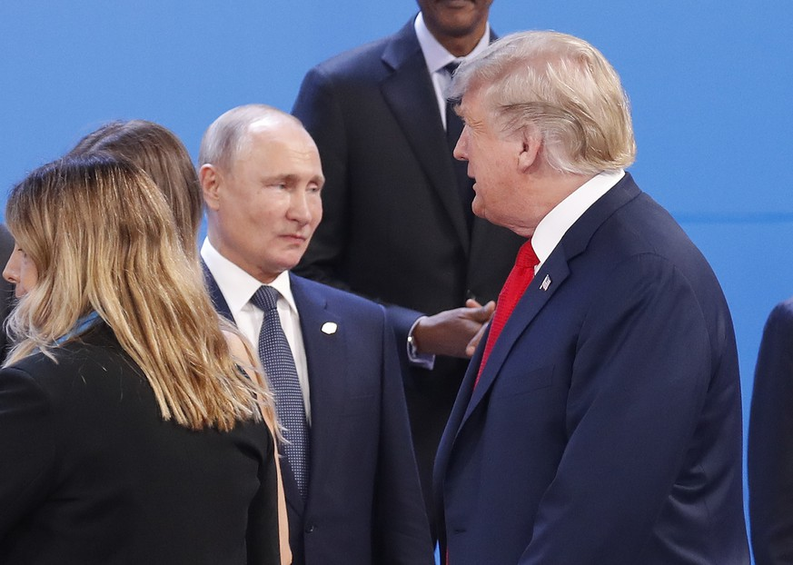 FILE - In this Nov. 30, 2018, file photo, President Donald Trump, right, walk past Russia's President Vladimir Putin, left, as they gather for the group photo at the start of the G20 summit in Buenos Aires, Argentina. For the past three years, the administration has careered between President Donald Trump's attempts to curry favor and friendship with Vladimir Putin and longstanding deep-seated concerns about Putin's intentions. (AP Photo/Pablo Martinez Monsivais, File) Donald Trump,Vladimir Putin