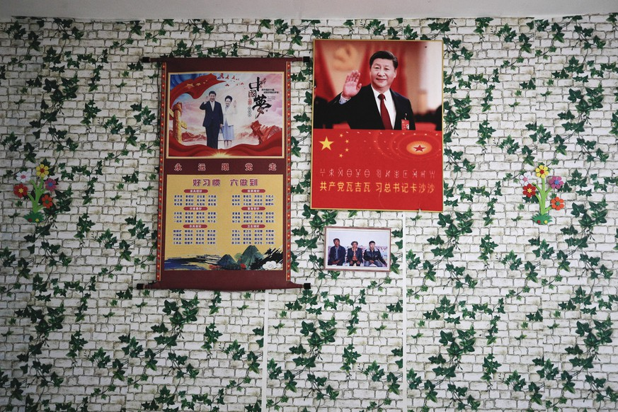 Posters of Chinese President Xi Jinping and his wife Peng Liyuan are displayed on a wall with a photo of members of the Yi minority group inside their home in Xujiashan village in Ganluo County, southwest China's Sichuan province on Sept. 10, 2020. Communist Party Xi