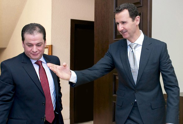 epa04247828 A photo released by Syrian Arab News Agency (SANA) shows Syrian President Bashar Assad (R) meeting with former presidential candidate, Maher al-Hajjar (L) in Damascus, Syria, 10 June 2014. Embattled Syrian President Bashar al-Assad scored an expected victory in presidential elections, securing a third seven-year as head of state amid a civil war engulfing the country.  Assad was running against only two little-known politicians; Hassan al-Nuri and Maher al-Hajjar.  EPA/SANA HANDOUT  HANDOUT EDITORIAL USE ONLY/NO SALES