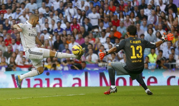 "Real Madrid's Karim Benzema (L) tries to score against Barcelona's goalkeeper Claudio Bravo during their Spanish first division ""Clasico"" soccer match at the Santiago Bernabeu stadium in Madrid October 25, 2014.      REUTERS/Juan Medina (SPAIN  - Tags: SOCCER SPORT)"