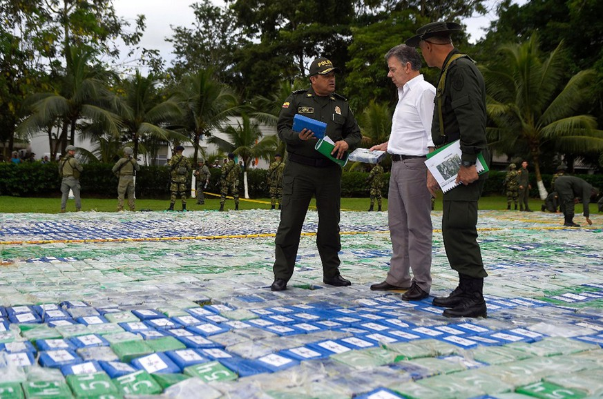 epa06316705 A handout photo made available by the Presidency of Colombiashows the Colombian President Juan Manuel Santos (C) speaking with police in the middle of packages containing cocaine, in Apartado, in the Department of Antioquia, Colombia, 08 November 2017.  Colombian authorities seized more than 12 tons of cocaine belonging to the Gulf Clan in the department of Antioquia (northwest), the country's largest criminal gang, Colombian President Juan Manuel Santos said.  EPA/Efrain Herrera PRESIDENCY OF COLOMBIA HANDOUT  HANDOUT EDITORIAL USE ONLY/NO SALES