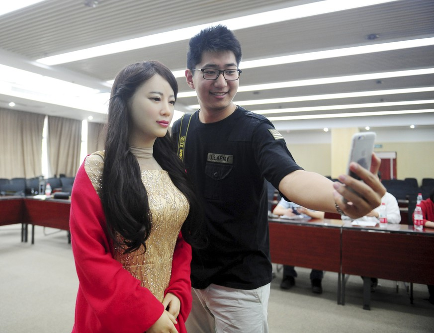 A man takes pictures with humanoid robot Jiajia produced by University of Science and Technology of China, at Jiajia's launch event in Hefei, Anhui province, April 15, 2016. REUTERS/Stringer ATTENTION EDITORS - THIS PICTURE WAS PROVIDED BY A THIRD PARTY. THIS PICTURE IS DISTRIBUTED EXACTLY AS RECEIVED BY REUTERS, AS A SERVICE TO CLIENTS. CHINA OUT. NO COMMERCIAL OR EDITORIAL SALES IN CHINA.      TPX IMAGES OF THE DAY