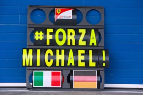 epa04046655 A pit board with the lettering '#FORZA MICHAEL' seen in front of the teamgarage of Ferrari during the training session for the upcoming Formula One season at the Jerez racetrack in Jerez de la Frontera, Southern Spain, 29 January 2014. Michael Schumacher's manager declined to comment 29 January on reports that doctors in France have begun the process of bringing the Formula One legend out of an artificial coma, one month since his skiing accident.  EPA/JENS BUETTNER -