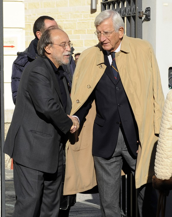 Bernardo De Bernardinis, former deputy chief of the Italian Civil protection technical department,  left, shakes hands with Genoa university physics professor Claudio Eva as they leave an appeal court building at the end of a hearing, in L'Aquila, Italy, Friday, Oct. 31, 2014.  An Italian appeal court is expected to pronounce itself in the next days over a previous 2012 verdict that convicted seven scientists and experts, members of the Italian