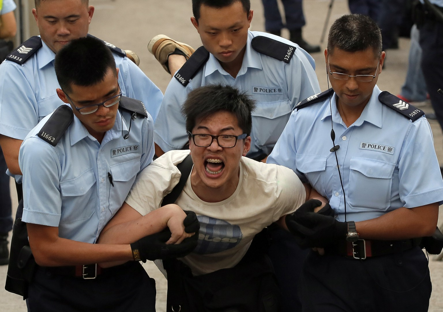 A protester, center, is taken away by police officers after hundreds of protesters staged a peaceful sit-ins overnight on a street in the financial district in Hong Kong Wednesday, July 2, 2014, following a huge rally to show their support for democratic reform and oppose Beijing's desire to have the final say on candidates for the chief executive's job. (AP Photo/Vincent Yu)