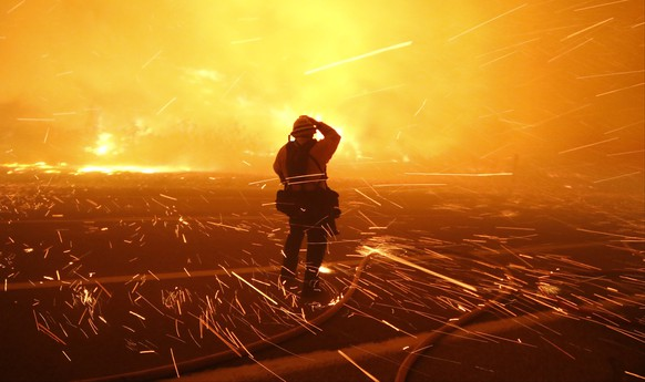 Fire photographer Tod Sudmeier gets hit with flying embers from strong winds at the Solimar brush fire that started early Saturday morning in Ventura County, California December 26, 2015. A wildfire in Southern California burned over 1,000 acres of land, forced the closure of parts of two major highways and led to evacuations on Saturday, fire officials said. REUTERS/Gene Blevins  TPX IMAGES OF THE DAY