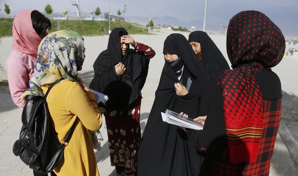 epa05988914 Female members of Afghanistan's first women magazine talk with burqa clad women as they introduce them to Gellara magazine in Kabul, Afghanistan, 23 May 2017 (issued 25 May 2017). Fatana Hassanzada, an Afghan woman together with seven female colleagues founded Afghanistan's first women's magazine, Gellara, defying cultural barriers in a male dominant society. Gellara covers topics like interviews with Afghan female artist and singers as well as fashion tips for women.  EPA/JAWAD JALALI