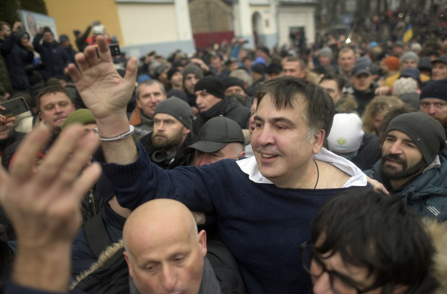 Former Georgian president Mikheil Saakashvili, center, greets protesters after he escaped with help from supporters and led them on a march toward parliament, where they planned to call for President Petro Poroshenko to resign in Kiev, Ukraine, Tuesday, Dec. 5, 2017. Hundreds of protesters chanting